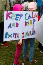 "Two young girls hold their sign ""Keep Calm and Keep Experimenting"" at the beginning of the march. Photo by Lauren Anikis 4/22/17"