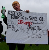 "One protestor dresses as Donald Trump, holding a water bottle labeled ""Snake Oil."" Photo by Lauren Anikis 4/22/17"